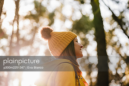 Smiling woman in knit hat looking away in forest - p300m2251347 by Eva Blanco
