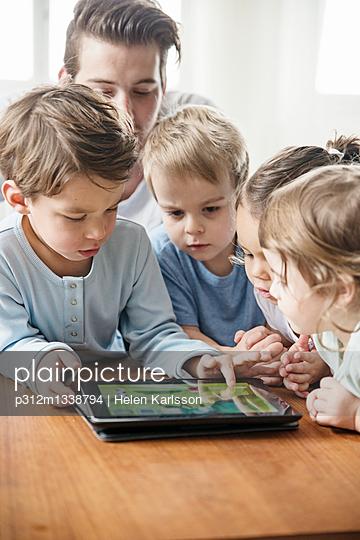 Male preschool teacher with tablet on preschool