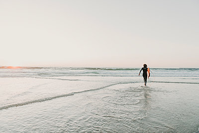 Rear view of running surfer on the beach at sunset, Costa Nova, Portugal - p300m2139615 by Hernandez and Sorokina