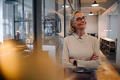 Portrait of smiling mature businesswoman leaning against glass pane in office - p300m2156086 by Gustafsson