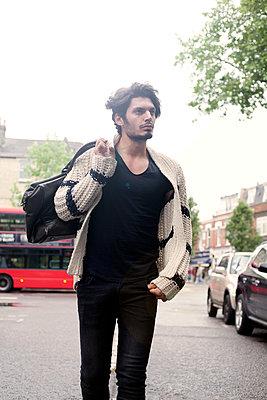 Young man walking down the road, London, United Kingdom - p300m2273634 von LOUIS CHRISTIAN