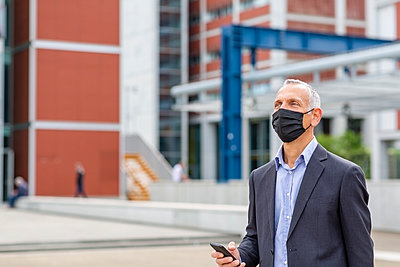 Senior man with face mask and mobile phone walking to work; Florence, Italy - p300m2287539 von Emma Innocenti