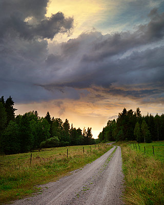 Dark clouds over farm track - p972m1136636 by Felix Odell