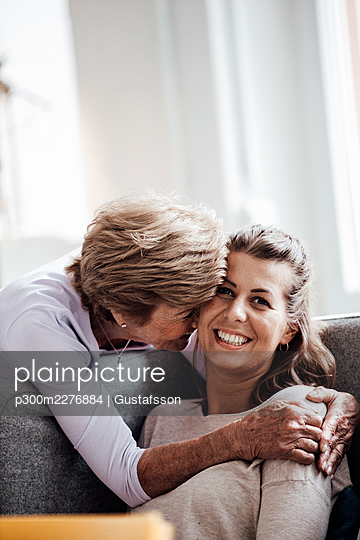 Loving grandmother embracing smiling woman while sitting on sofa at home - p300m2276884 by Gustafsson