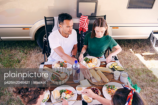 High angle view of parents and children having food at table in campsite - p426m2046421 by Maskot