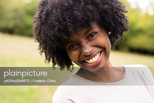 Close-up of smiling young woman standing in park - p623m2294870 by Frederic Cirou