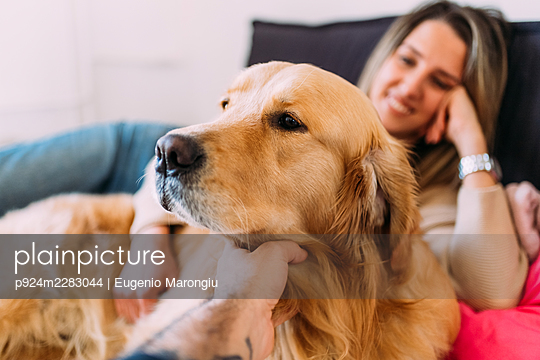 Italy, Young woman and dog relaxing on bed - p924m2283044 by Eugenio Marongiu