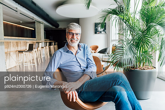 Italy, Portrait of smiling man sitting in armchair in creative studio - p924m2300726 by Eugenio Marongiu