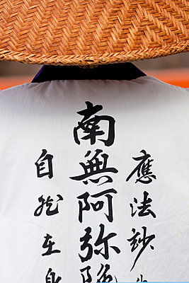 Rear view of Buddhist nun wearing traditional clothing and straw hat. - p1100m1520341 by Mint Images