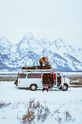 Couple decorate their van with christmas tree and dog - p1166m2078403 by Cavan Images