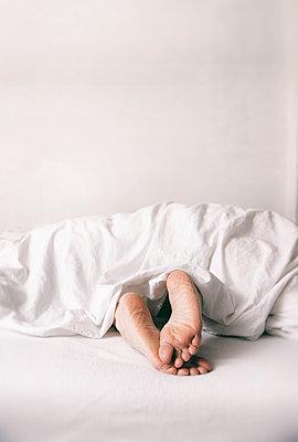 Frauenfüße aus der Bettdecke - Bauchlage - p1212m1116022 von harry + lidy