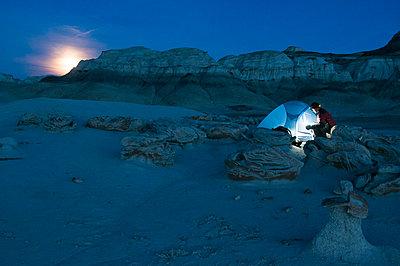 A man setting up a tent at night, Bisti Badlands, Farmington, New Mexico. - p1424m1501614 by Kennan Harvey