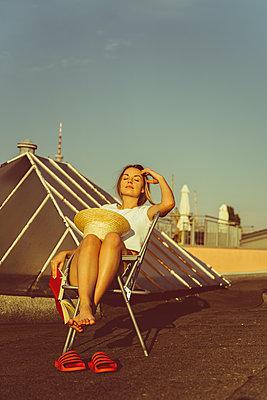 Junge Frau sitzt entspannt mit Buch auf Hausdach - p432m2260297 von mia takahara
