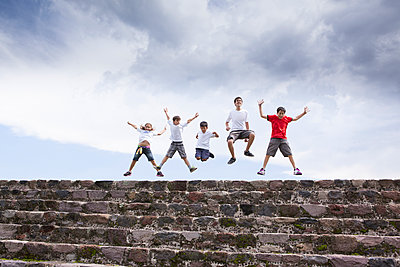 Children jumping on top of steps - p555m1478633 by Sollina Images