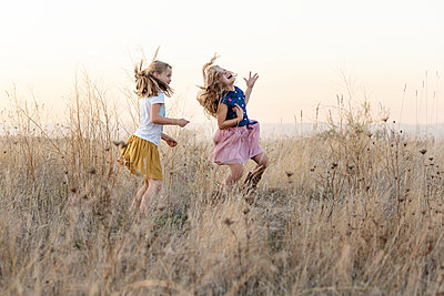 Two girls in field - p712m2173958 by Jana Kay