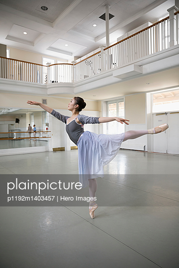 Graceful female ballet dancer practicing in dance studio - p1192m1403457 by Hero Images