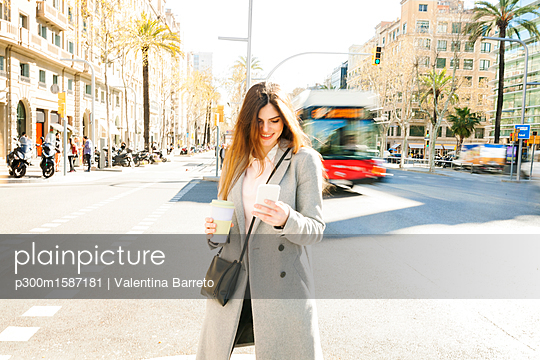 Spain, Barcelona, smiling young woman with coffee to go standing at roadside looking at cell phone - p300m1587181 von Valentina Barreto