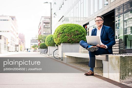 Mature businessman using laptop on bench outdoors - p300m2004532 von Joseffson