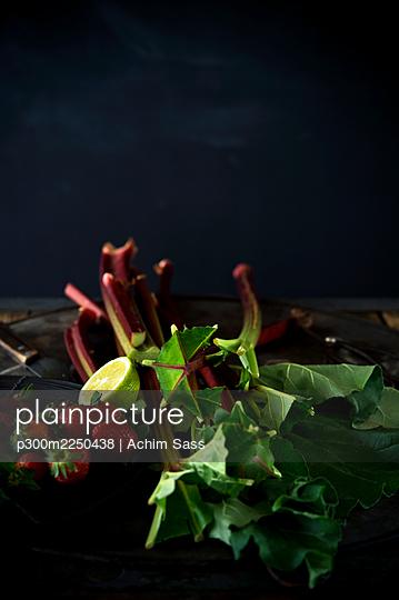 Studio shot of fresh rhubarb stalks, strawberries and halved lime - p300m2250438 by Achim Sass