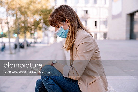 Young woman with protective face mask using smart phone while sitting outside - p300m2264681 by Albert Martínez