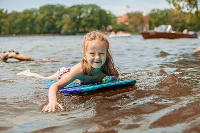 Mädchen schwimmt auf einem Bodyboard am See - p1394m1541476 von benjamin tafel