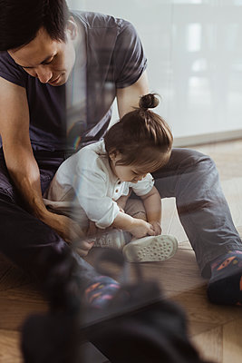 Baby son tying shoelace sitting with father at home - p426m2238195 by Maskot