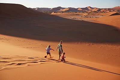 Mother and sons walking on sand dune, Namib Naukluft National Park, Namib Desert, Sossusvlei, Dead Vlei, Africa - p429m1029735 by Stephen Lux