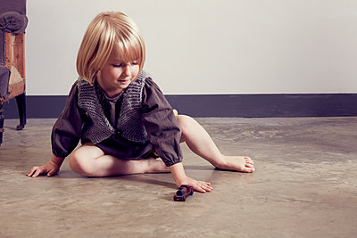 Girl playing on floor with old wooden toy locomotive - p429m1408165 by Emma Kim
