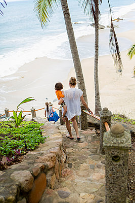 Caucasian mother carrying son descending staircase to beach - p555m1305326 by Marc Romanelli