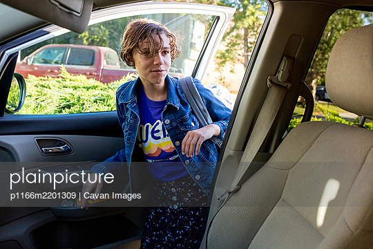Teen girl with short hair gets into the car with her backpack - p1166m2201309 by Cavan Images