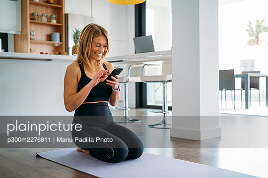 Woman using smart phone while kneeling on exercise mat at home - p300m2276911 by Manu Padilla Photo