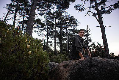 Hiker rests on boulder at the edge of the forest - p1640m2261040 by Holly & John