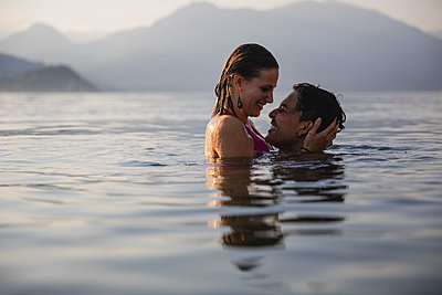 Happy affectionate young couple in a lake - p300m2042936 von Michela Ravasio