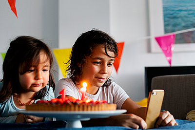 Portrait of boy and his little sister celebrating birthday with cake at home - p300m2189574 by Valentina Barreto