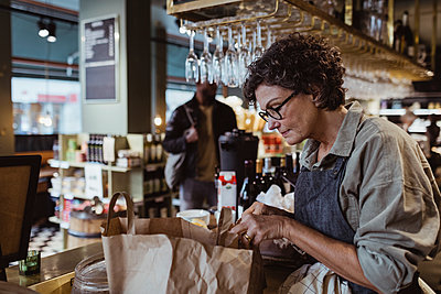 Female owner packing order in paper bag at delicatessen shop - p426m2270620 by Maskot