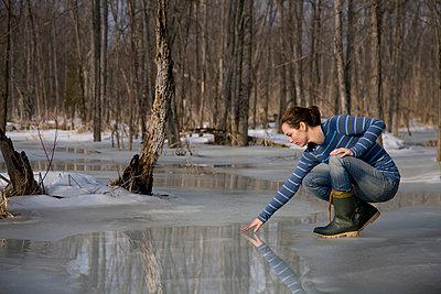 Woman Testing Melting Ice on Pond - p4295757 by Hugh Whitaker