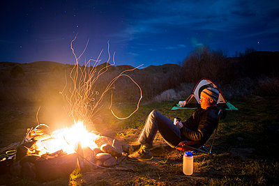 Caucasian man relaxing near campfire in remote field, Painted Hills, Oregon, United States - p555m1412147 by Adam Hester