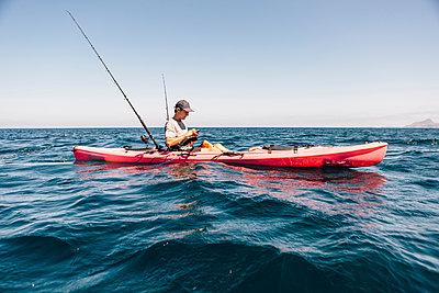 Young male sea kayaker looking at smartphone while fishing, Santa Cruz Island, California, USA - p924m1506722 by JFCreatives