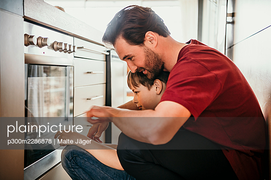 Father with son looking in oven while preparing food - p300m2286878 by Malte Jäger