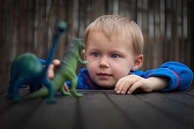 Junge spielt mit Dinosauriern - p105m902756 von André Schuster