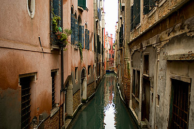 A view from above of a quiet backwater, a narrow canal with historic buildings rising from the water.  - p1100m991388f by Mint Images