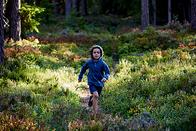 Boy running across clearing in the woods - p1511m2223075 by artwall