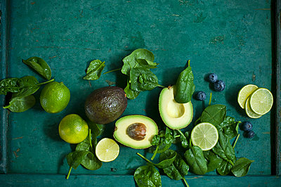Spinach leaves, avocados and blueberries on green ground - p300m1587173 von Achim Sass