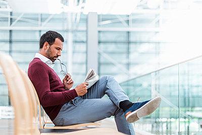 Businessman reading a newspaper in waiting hall - p300m1588179 von Daniel Ingold