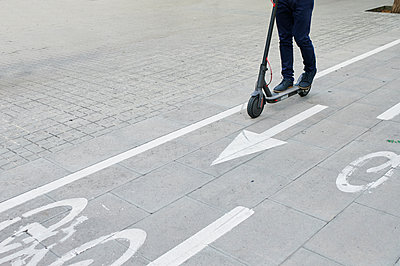 Legs of man riding e-scooter on bicycle lane in the city - p300m2143815 by Ivan Gener