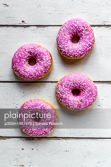 Four pink doughnuts on white wood - p300m1587472 von Sandra Roesch