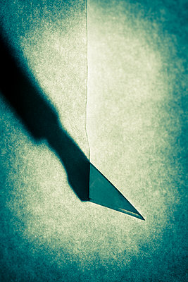 Close up of a scalpel knife slicing paper - p1057m2008588 by Stephen Shepherd