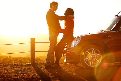 Couple embracing while standing by car on field against sky - p1166m1096120f by Cavan Images