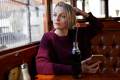 Portrait of blond woman in a cafe looking out of window - p300m2012932 von Philipp Nemenz