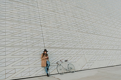 Young hipster woman holding smartphone near to a bicycle - p300m2102631 von Hernandez and Sorokina